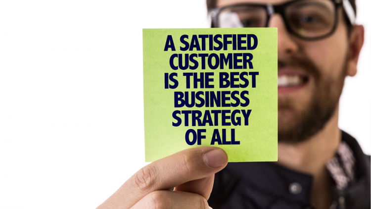 Man holding a sticky note that reads A satisfied customer is the best business strategy of all