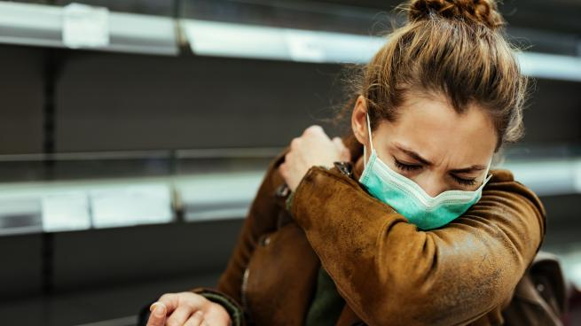 woman wearing a mask and coughing into her sleeve