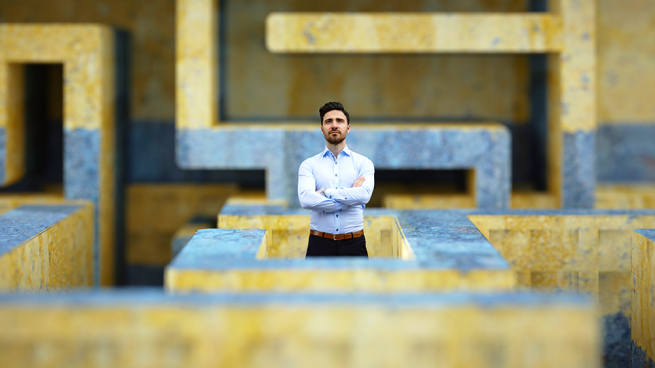 Man standing in the middle of a large, concrete maze