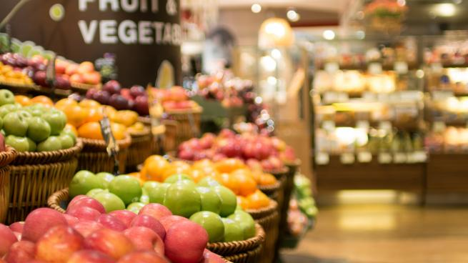 a store filled with lots of fruit and vegetables on display